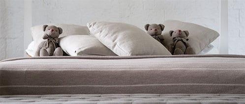 Oreillers et peluches sur un lit